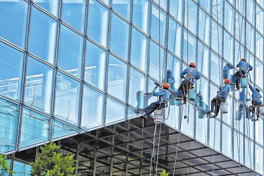 Professionelle Fensterputzer bei der Arbeit. Veredelte und reflexionsmindernde Scheiben wie an vielen Bürogebäuden erfordern besondere Sorgfalt. Foto: Fotolia/PeterHaas